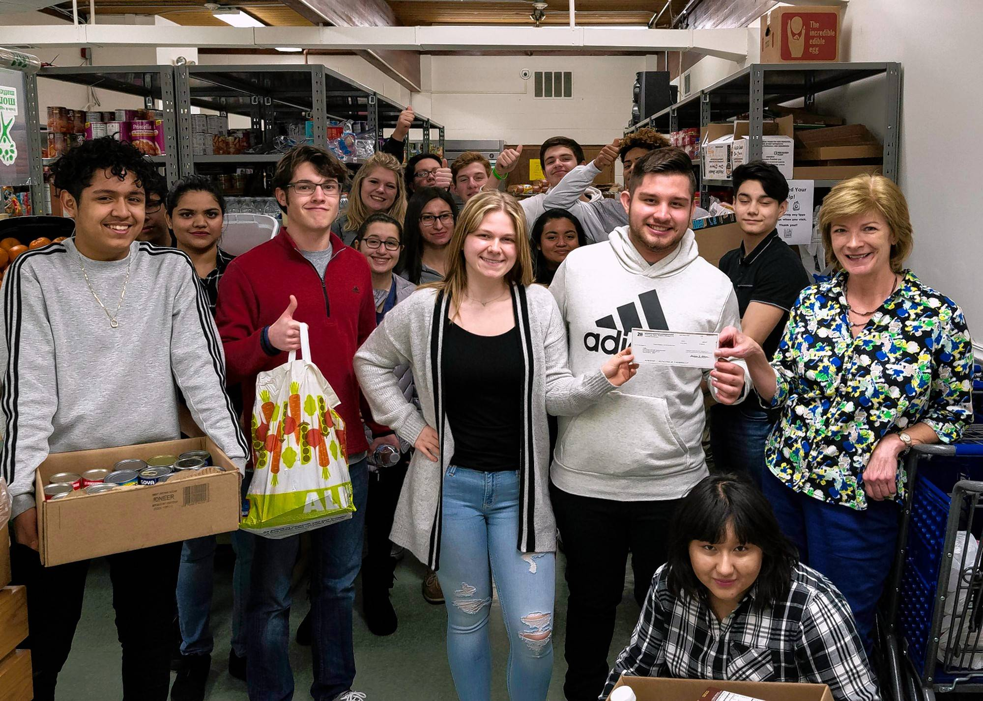 Students from Palatine High School's Chemistry of Foods class present a check for $400 and food to the Palatine Township Food Pantry.