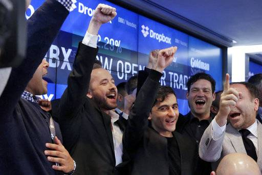 Dropbox co-founders Drew Houston, second left, and Arash Ferdowsi, third left, and company executives celebrate as their company's IPO begins trading at the Nasdaq MarketSite, in New York's Times Square, Friday, March 23, 2018. (AP Photo/Richard Drew)