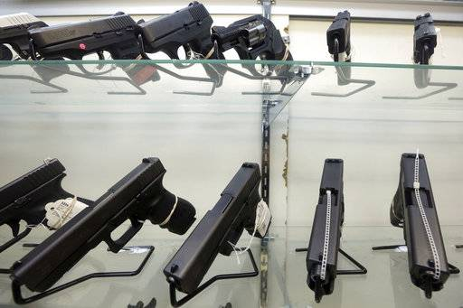 FILE - This June 29, 2016, file photo shows guns on display at a gun store in Miami. Support for tougher gun control laws is soaring in the United States, according to a new poll that found a majority of gun owners and half of Republicans favor new laws to address gun violence in the weeks after a Florida school shooting left 17 dead and sparked nationwide protests. (AP Photo/Alan Diaz, File)