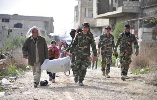 This photo released by the Syrian official news agency SANA, shows Syrian government soldiers, helping civilians who fled from fighting between the Syrian government forces and insurgents, through the Wafideen crossing in eastern Ghouta, a suburb of Damascus, Syria, Thursday, March 22, 2018. Syrian troops have recently taken control of about 80 percent of eastern Ghouta from rebel forces.(SANA via AP)