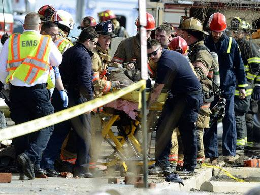 Emergency personnel move an injured firefighter to an ambulance after a wall collapse at the scene of a fire in York, Pa., Thursday, March 22, 2018. York officials said part of the four-story building fell on firefighters as they were looking for hot spots and investigating the cause of the fire that broke out Wednesday at the Weaver Organ and Piano factory. (John A. Pavoncello/York Dispatch via AP)