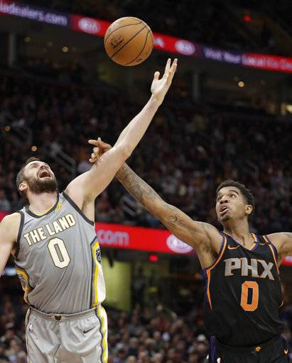 Cleveland Cavaliers' Kevin Love, left, and Phoenix Suns' Marquese Chriss reach for a rebound in the first half of an NBA basketball game Friday, March 23, 2018, in Cleveland. (AP Photo/Tony Dejak)