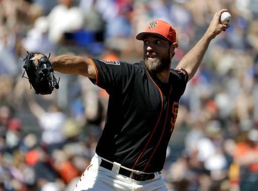 San Francisco Giants starting pitcher Madison Bumgarner throws against the Kansas City Royals during the first inning of a spring baseball game in Scottsdale, Ariz., Friday, March 23, 2018. (AP Photo/Chris Carlson)