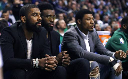 Boston Celtics guard Kyrie Irving, left, sit with teammates Jaylen Brown, center, and Marcus Smart during the first quarter of the team's NBA basketball game against the Oklahoma City Thunder in Boston, Tuesday, March 20, 2018. All three starters are sidelined with injuries. (AP Photo/Charles Krupa)