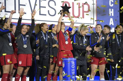 FILE - In this Wednesday, March 7, 2018 file photo, United States midfielder Carli Lloyd, center, lifts the championship trophy with teammates after defeating England 1-0, to win the SheBelieves Cup women's soccer tournament in Orlando, Fla. The United States stays top of the FIFA women's world rankings after winning the SheBelieves Cup, and England goes above Germany into second. The Americans went unbeaten through the four-team round-robin tournament it hosted this month. (AP Photo/Phelan M. Ebenhack, File)