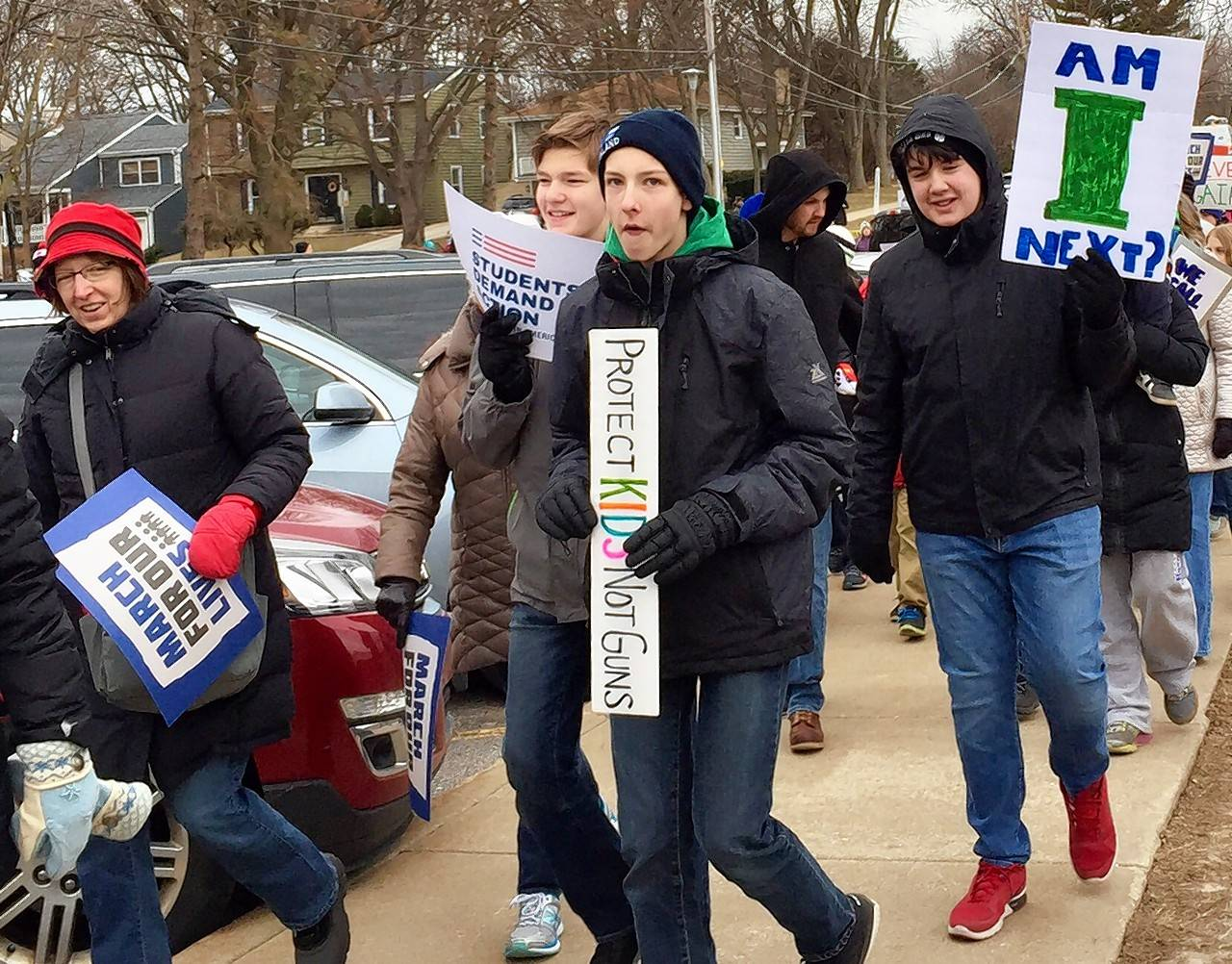 More than 1,000 people attended a gun violence protest Saturday in Glen Ellyn. It was among many going on in the Chicago area, with hundreds more around the world.