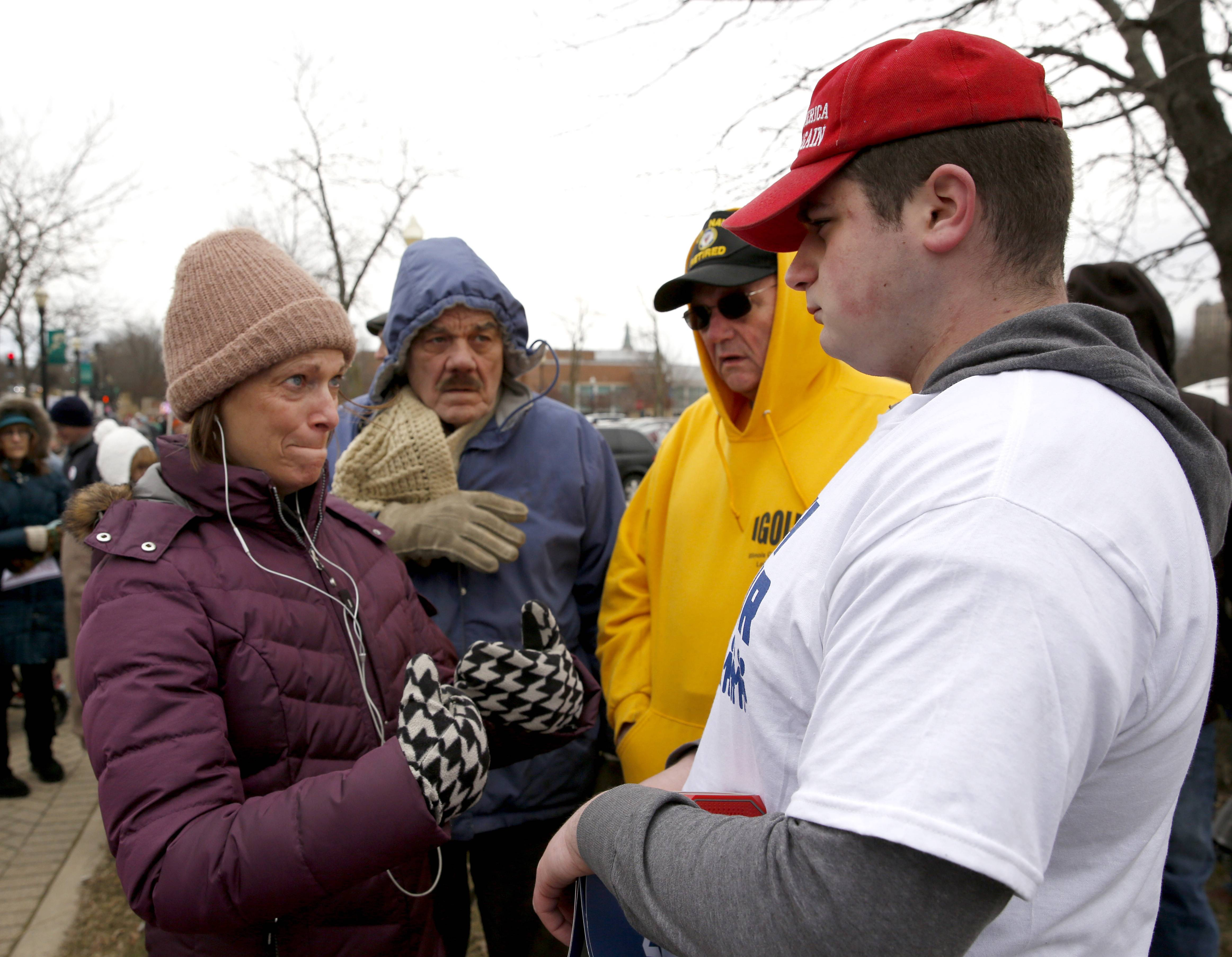 "Mary Lou Eubanks of Sycamore, left, tries to explain her views on gun control to Shawn Campbell of Elgin, right, before the March for Our Lives rally Saturday in downtown Elgin. ""Eight-nine percent of all mass shootings are done by people over the age of 21,"" Campbell said."