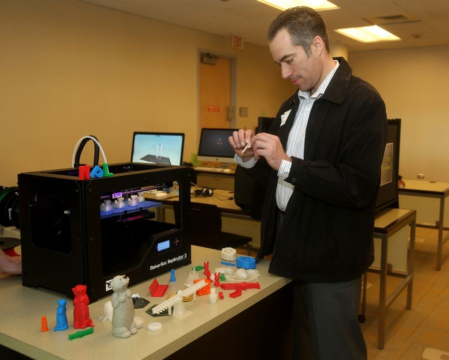 Keith Giaquinto examines items made by the 3-D printer in the Idea Lab at the 95th Street Library in Naperville.