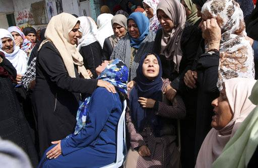 "Relatives mourn when they carry the body of Hamdan Abu Amsha, 23, during his funeral in front of his family house in Beit Hanoun, Gaza Strip, Saturday, March 31, 2018. Israel will target ""terror organizations"" in Gaza if violence along the territory's border with Israel drags on, the chief military spokesman warned Saturday, a day after thousands of Palestinians staged protests near the border fence."