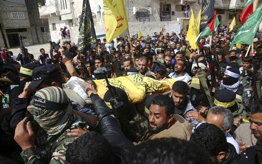 "Relatives and Fateh masked militants carry the body of Hamdan Abu Amsha, 23, during his funeral in Beit Hanoun, Gaza Strip, Saturday, March 31, 2018. Israel will target ""terror organizations"" in Gaza if violence along the territory's border with Israel drags on, the chief military spokesman warned Saturday, a day after thousands of Palestinians staged protests near the border fence."