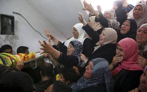 "Relatives mourn over the body of Hamdan Abu Amsha, 23, during his funeral at the family house in Beit Hanoun, Gaza Strip, Saturday, March 31, 2018. Israel will target ""terror organizations"" in Gaza if violence along the territory's border with Israel drags on, the chief military spokesman warned Saturday, a day after thousands of Palestinians staged protests near the border fence."