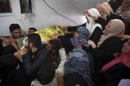 "Relatives mourn as they carry the body of Hamdan Abu Amsha, 23, during his funeral at his family house in Beit Hanoun, Gaza Strip, Saturday, March 31, 2018. Israel will target ""terror organizations"" in Gaza if violence along the territory's border with Israel drags on, the chief military spokesman warned Saturday, a day after thousands of Palestinians staged protests near the border fence."