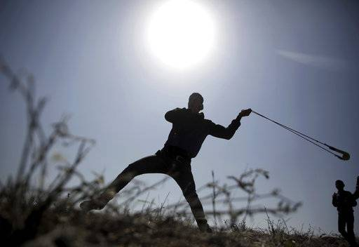 A Palestinian protester hurls stones toward Israeli soldiers during a protest near the Gaza Strip border with Israel, in eastern Gaza City, Saturday, March 31, 2018.