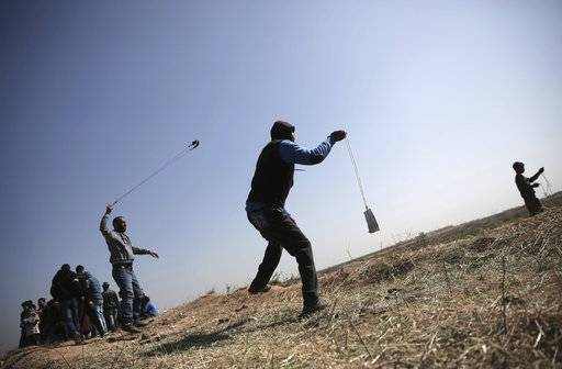 Palestinians hurl stones toward Israeli soldiers during a protest near the Gaza Strip border with Israel, in eastern Gaza City, Saturday, March 31, 2018.