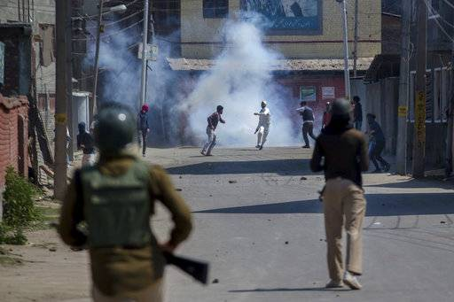 Kashmiri protesters engulfed in tear gas smoke clash with Indian paramilitary soldiers during a protest against the killing of rebels in Srinagar, Indian controlled Kashmir, Sunday, April 1, 2018. At least eight rebels have been killed in fighting with Indian troops in disputed Kashmir, triggering a new round of anti-India protests and clashes, officials said Sunday.