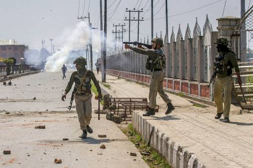 Indian paramilitary soldier center, fires tear gas shell towards Kashmiri protester during a protest against the killing of rebels in Srinagar, Indian controlled Kashmir, Sunday, April 1, 2018. At least eight rebels have been killed in fighting with Indian troops in disputed Kashmir, triggering a new round of anti-India protests and clashes, officials said Sunday.
