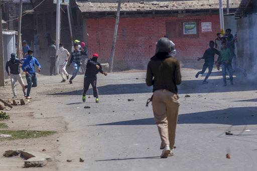 Kashmiri protesters throw stones and bricks at Indian paramilitary soldier during a protest against the killing of rebels in Srinagar, Indian controlled Kashmir, Sunday, April 1, 2018. At least eight rebels have been killed in fighting with Indian troops in disputed Kashmir, triggering a new round of anti-India protests and clashes, officials said Sunday.