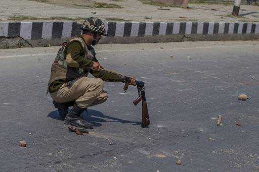 An Indian paramilitary soldier uses a piece of wood to remove a tear gas shell jammed in his gun during a protest against the killing of rebels in Srinagar, Indian controlled Kashmir, Sunday, April 1, 2018. Deadly protests against Indian rule erupted in several parts of Indian-controlled Kashmir on Sunday following the killings of at least eight rebels in fighting with government forces, officials said.
