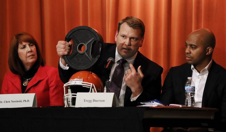Dr. Chris Nowinski uses a heavy weight to demonstrate the impact on a helmet Monday at the Sullivan Center in Vernon Hills. State Rep. Carol Sente, sponsor of the bill, sits at left /and Tregg Duerson, son of former Chicago Bear Dave Duerson, sits at right.