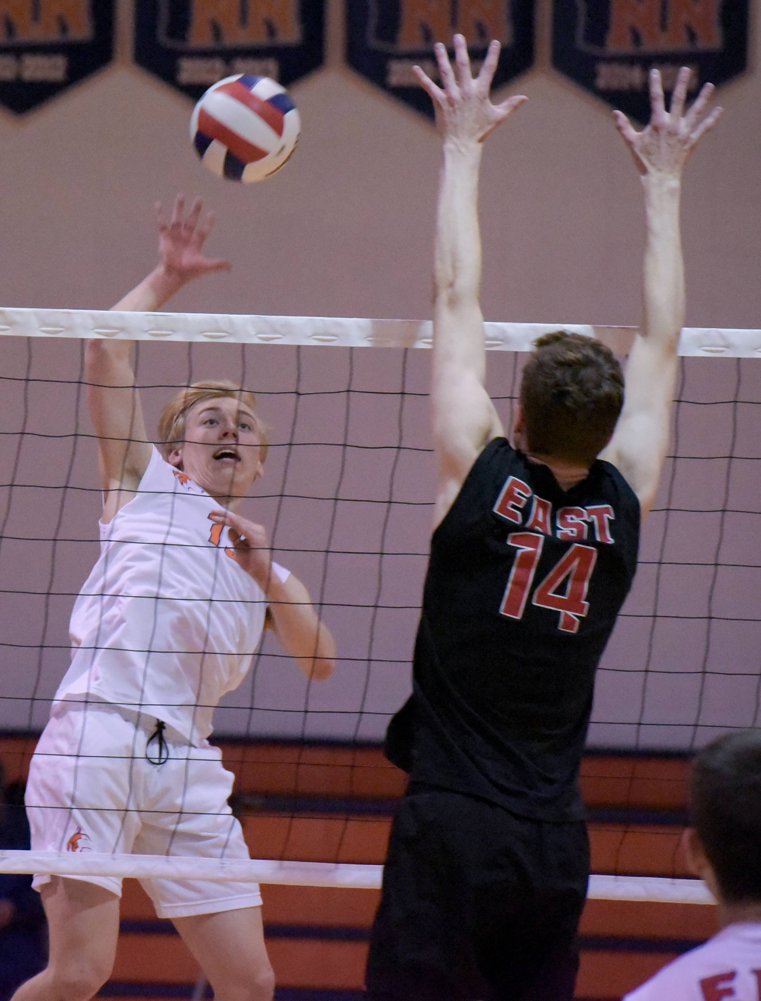 Naperville North's John Jaworski (13) fires a shot past Glenbard East's Carson Brandt (14) during boys volleyball in Naperville on Tuesday, April 3, 2018.