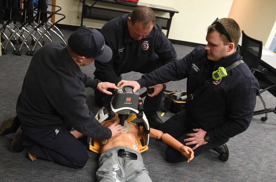 "Elgin firefighters Jeff Lynskey, left, Shay Brill and Patrick Wiebe demonstrate one of the ""Lucas 3"" automated CPR devices that the Elgin Fire Department acquired last year. Successful resuscitations nearly doubled in months when the devices were in use."