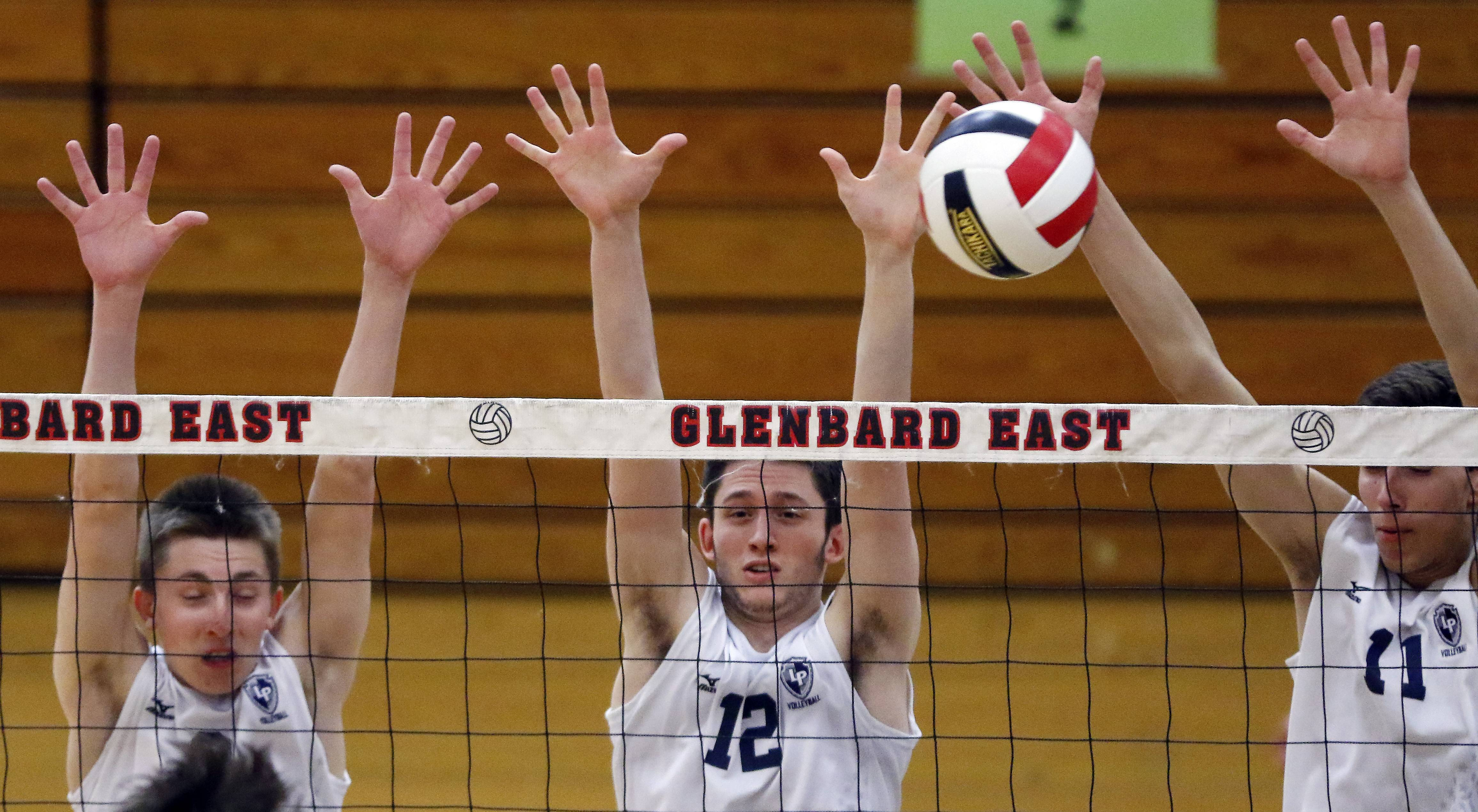 Lake Park's Bob Sampson, from left, Austin Bayner, and Nick Martinski try to block a Glenbard West shot during the Springfest boys volleyball tournament Saturday at Glenbard East High School in Lombard.