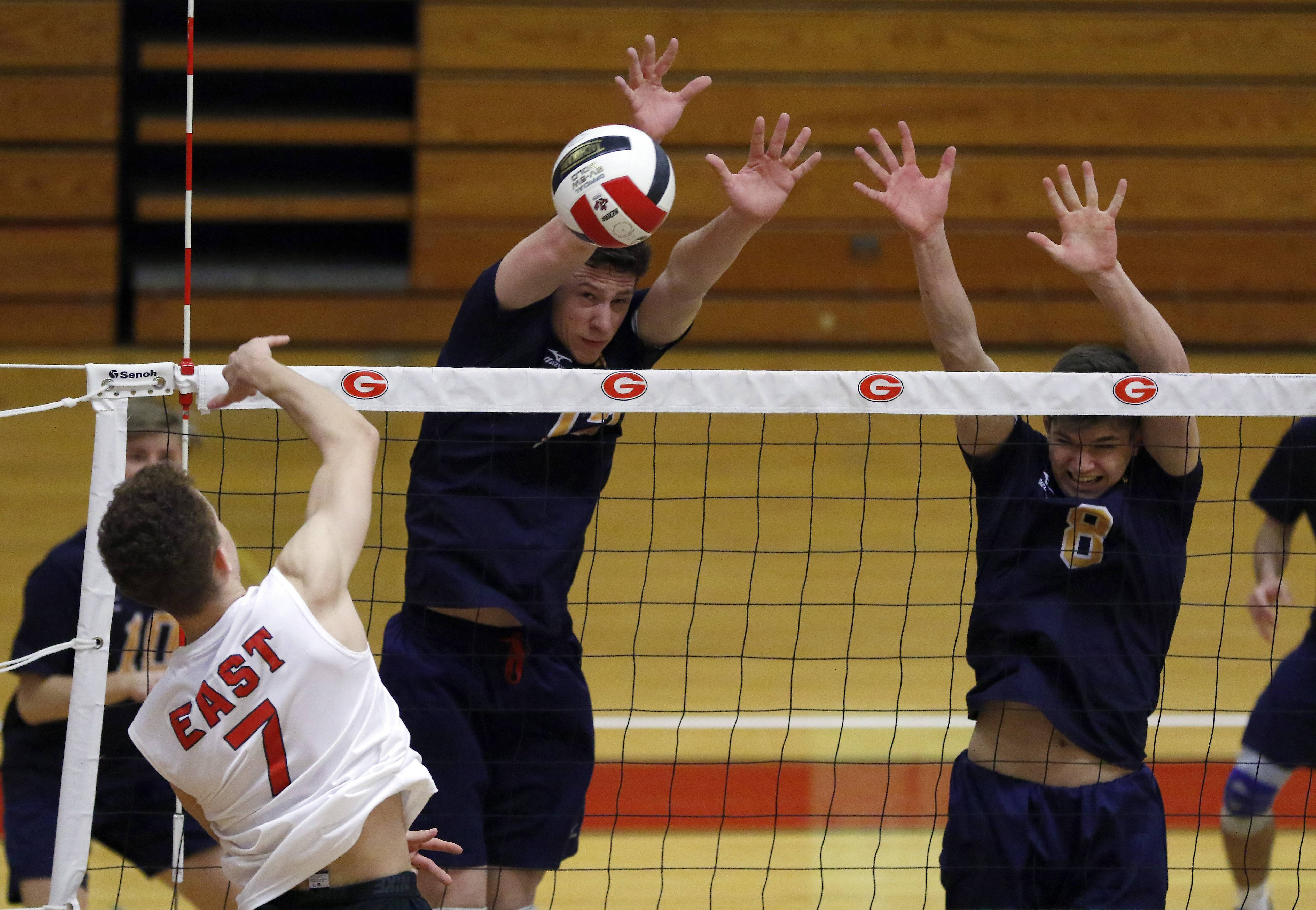 Glenbard East's Matt Smith hits a shot against Neuqua Valley's Kevin Kauling, left, and Ryan McGladdery during the Springfest boys volleyball tournament Saturday at Glenbard East High School in Lombard.