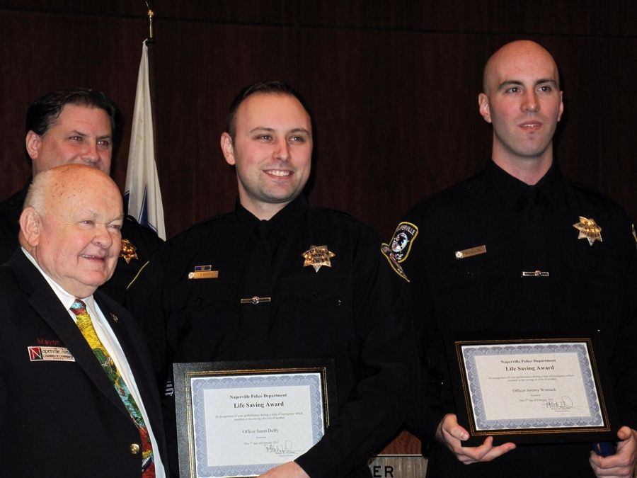 Naperville police officer Jason Duffy, center, has received the Lifesaving Award three times since 2015 for reviving opioid users from overdoses using the nasal-spray antidote Narcan. His most recent award recognizes his role in an overdose revival on Jan. 11.