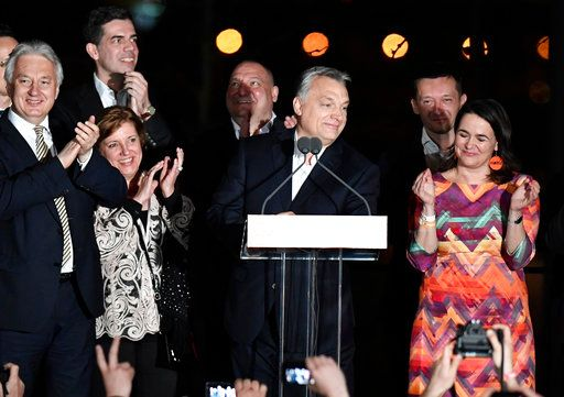 "Hungarian Prime Minister and Chairman of Fidesz Party Viktor Orban, center, and Deputy Prime Minister and Chairman of the Christian Democratic Party Zsolt Semjen, left, celebrate the win of Fidesz and the Christian Democrats at the election night watch event after the general elections in Budapest, Hungary, late Sunday, April 8, 2018.  Prime Minister Viktor Orban said his ""decisive"" re-election victory and the super majority in parliament his right-wing populist party appeared to have won Sunday were ""an opportunity to defend Hungary.""  (Szilard Koszticsak/MTI via AP)"