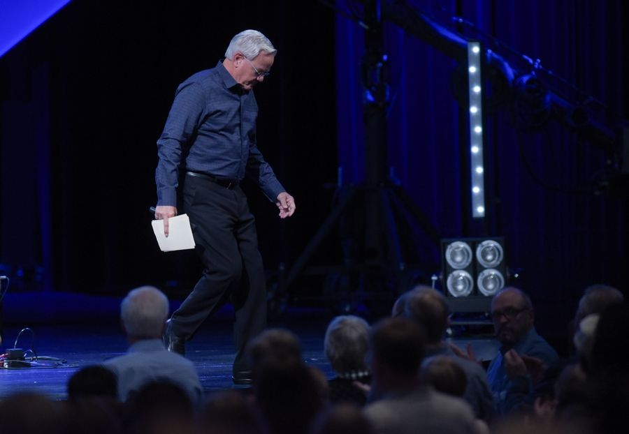 Senior Pastor Bill Hybels walks off the stage after making the announcement he is stepping down as lead pastor of Willow Community Church effective immediately.