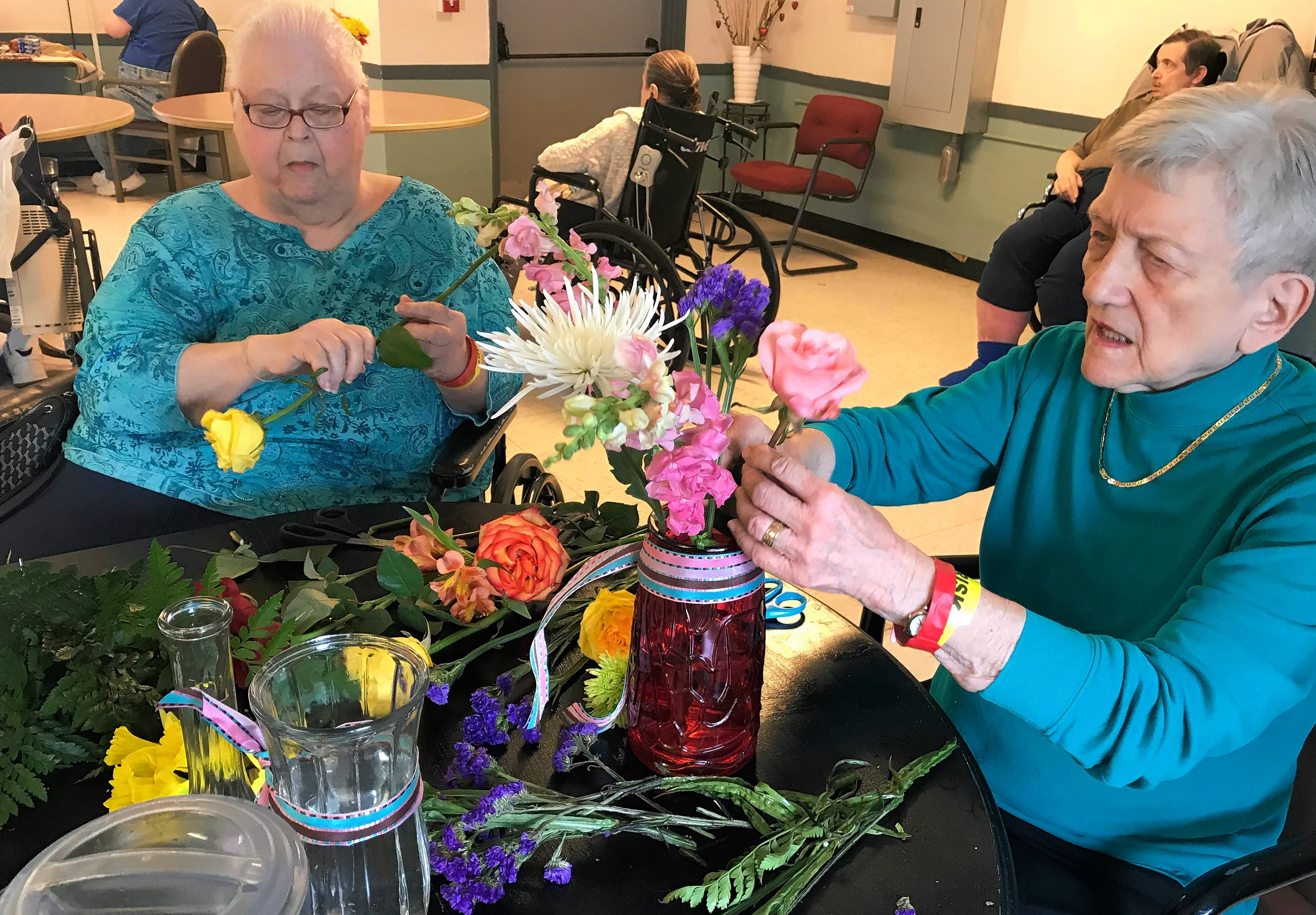Bonnie Clemenson, left, and Sue Lamie, residents of South Elgin Rehabilitation & Health Care Center, said they enjoy making flower arrangements thanks to a weekly donation from florist Debi's Designs.
