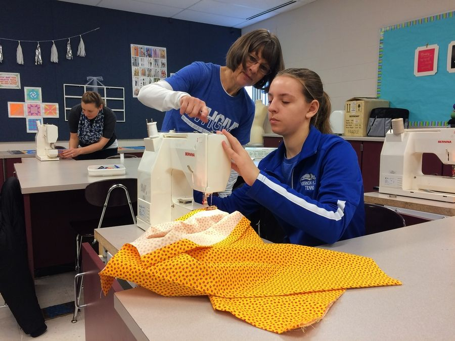 With help from secretary Ruth Netland, Vernon Hills High School freshman Chantal Korde sews a dress as part of a volunteer project Tuesday.