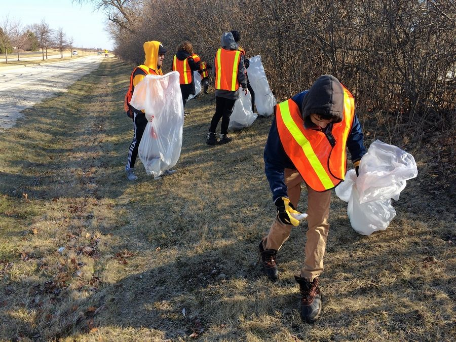 Vernon Hills High School freshman Jad Salhani, far right, and other students gather trash along Fairway Drive as part of a volunteer service project Tuesday.