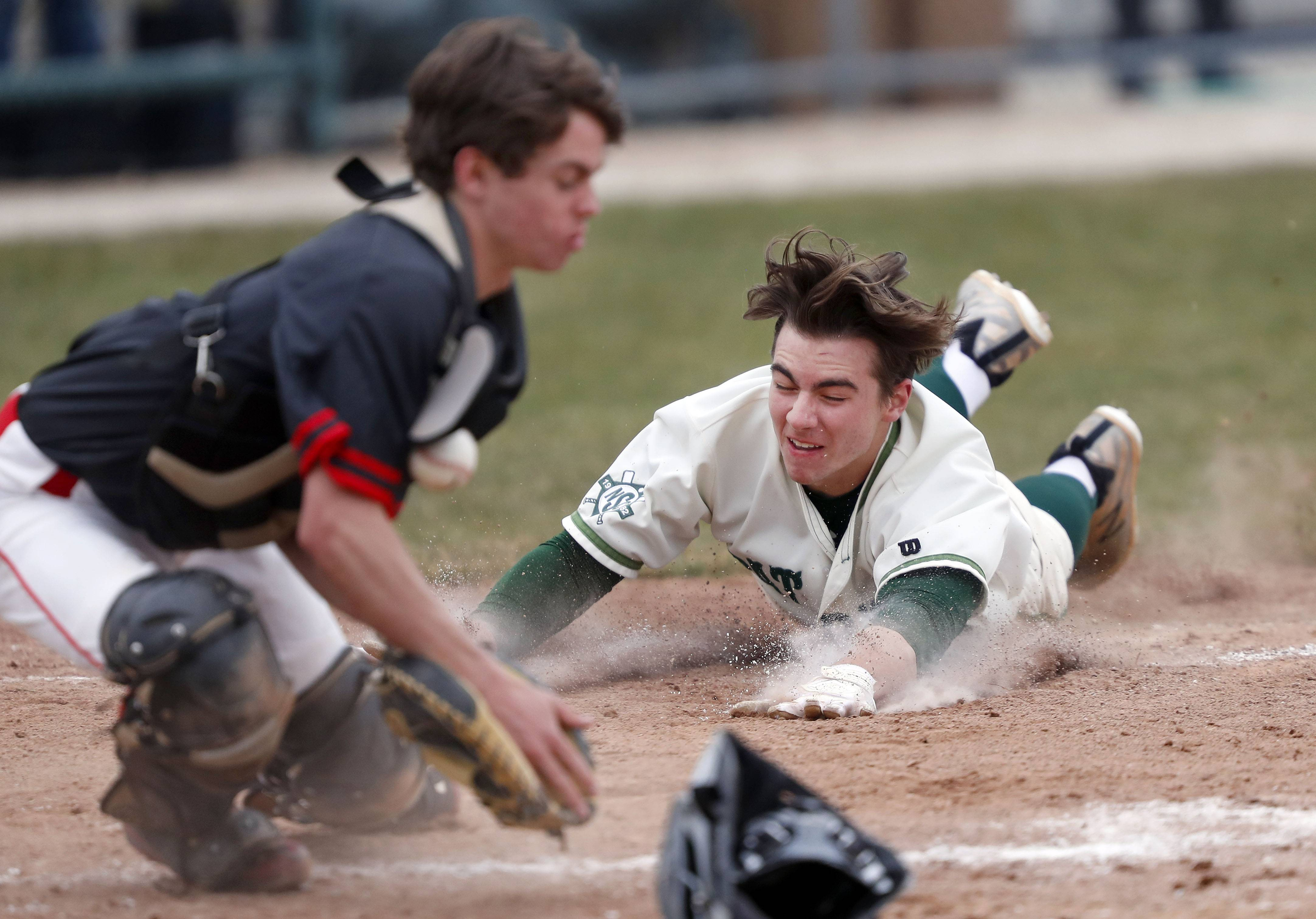 Stevenson's Ryan McElhinny, right, scores as Mundelein's Mason Schaller waits for the throw to the plate Wednesday in Lincolnshire.