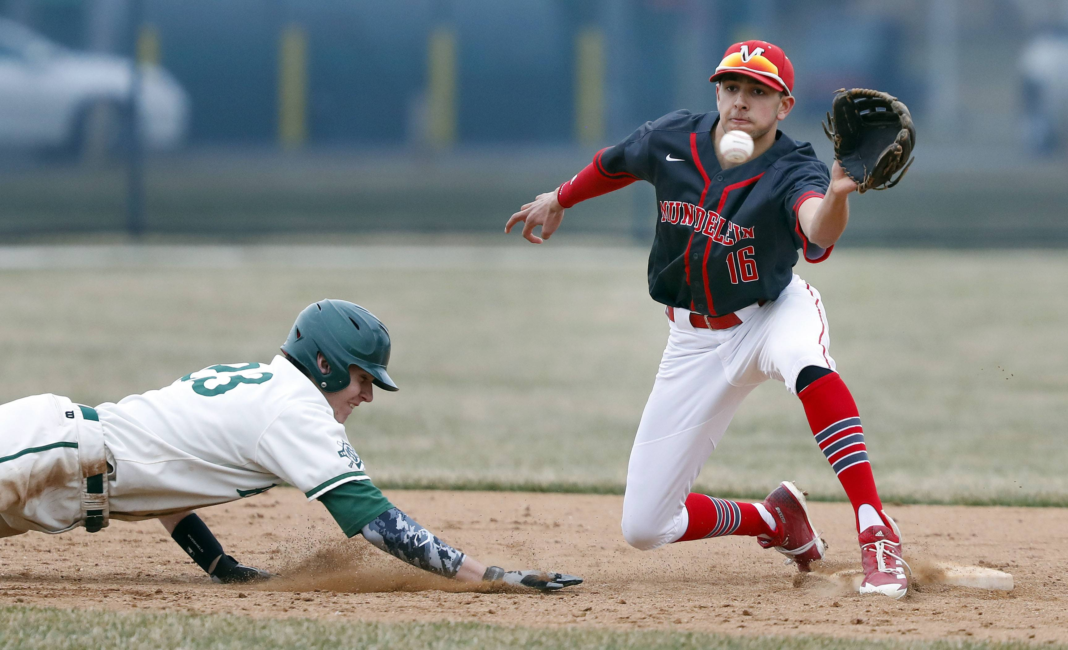 Stevenson's Nicholas Bonk dives back to second safely as Mundelein's Ryan Patel makes the play Wednesday in Lincolnshire.