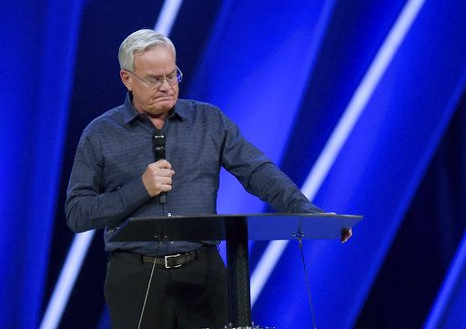 Willow Creek Community Church Senior Pastor Bill Hybels stands before his congregation, Tuesday, April 10, 2018, in South Barrington, Ill., where he announced his early retirement effective immediately, amid a cloud of misconduct allegations involving women in his congregation. The announcement was made during a special meeting at the church, one of the nation's largest evangelical churches, which he founded. (Mark Black/Daily Herald via AP)