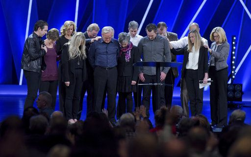 Willow Creek Community Church Senior Pastor Bill Hybels, sixth from left, and other church leaders pray before the congregation, Tuesday, April 10, 2018, in South Barrington, Ill., where Hybels announced his early retirement effective immediately, amid a cloud of misconduct allegations involving women in his congregation. The announcement was made during a special meeting at the church, one of the nation's largest evangelical churches, which Hybels founded. (Mark Black/Daily Herald via AP)