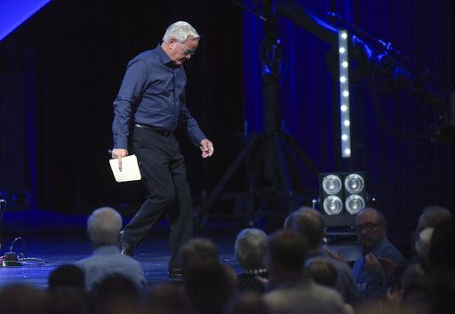 Willow Creek Community Church Senior Pastor Bill Hybels leaves the stage after speaking to his congregation, Tuesday, April 10, 2018, in South Barrington, Ill., where he announced his early retirement effective immediately, amid a cloud of misconduct allegations involving women in his congregation. The announcement was made during a special meeting at the church, one of the nation's largest evangelical churches, which he founded. (Mark Black/Daily Herald via AP)