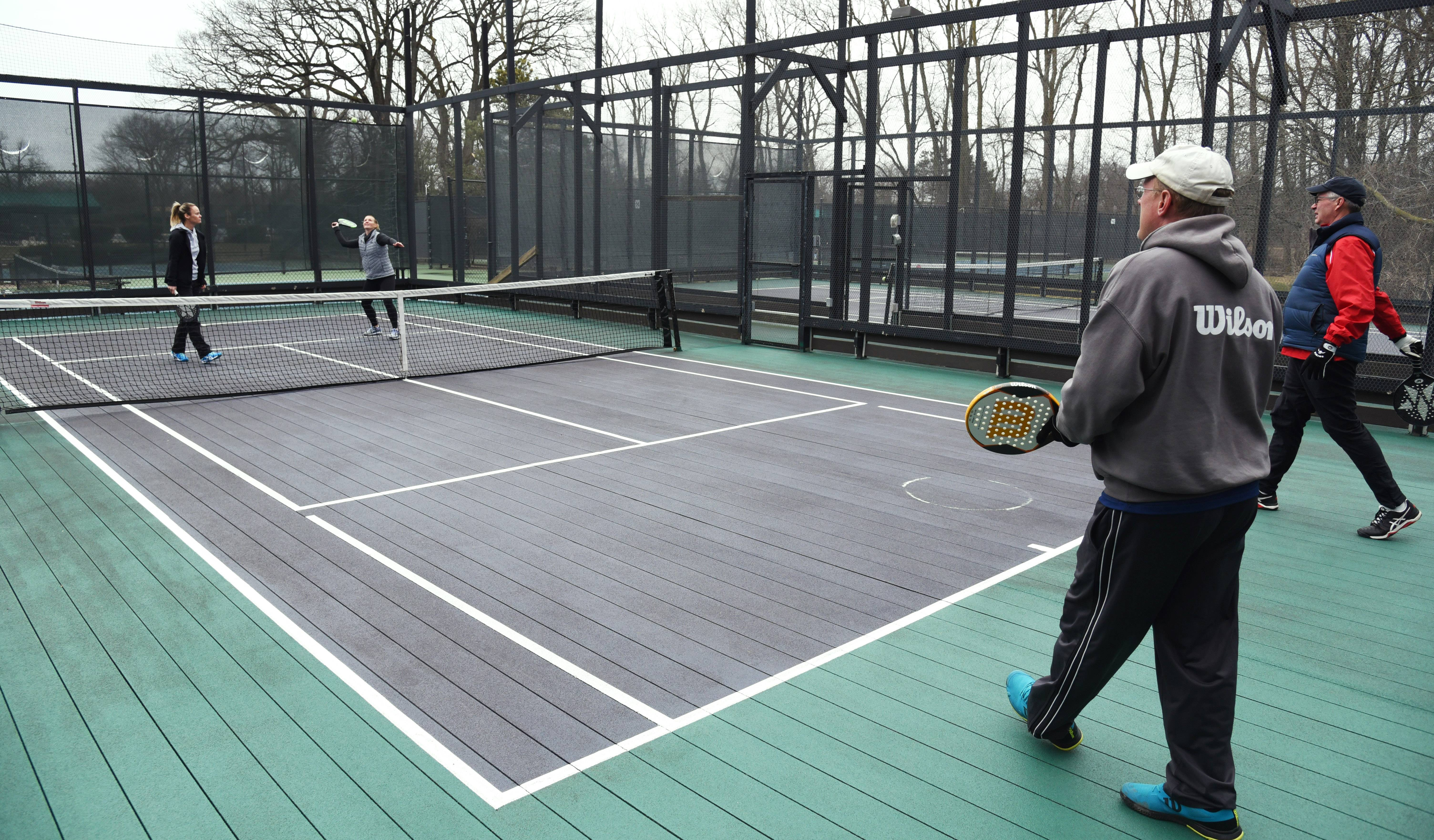 Platform tennis players Laura Berendt, left, and Alison Morgan play against Bjorn Bernhardtz and Mike Carrico, right, at the Birchwood Club in Highland Park.