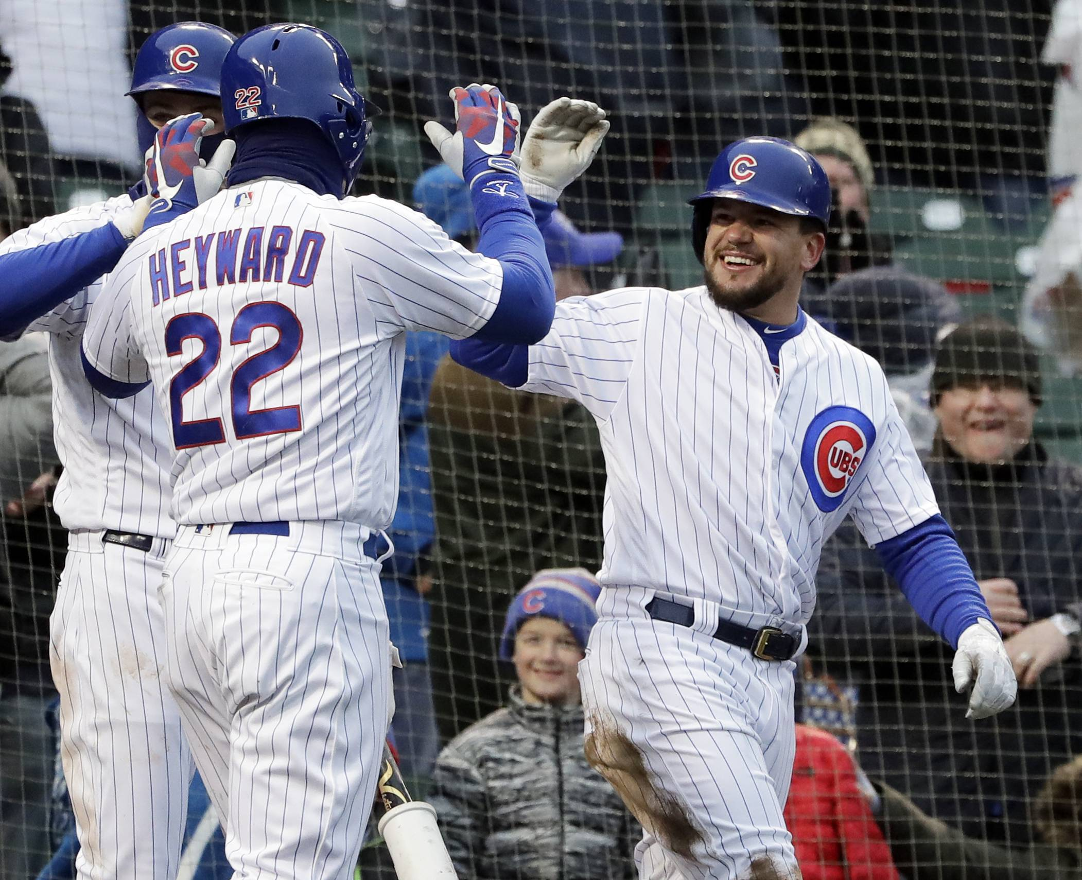 Chicago Cubs' Kyle Schwarber, right, celebrates with Jason Heyward (22) after they scored on a wild pitch by Atlanta Braves relief pitcher Peter Moylan during the eighth inning Saturday at Wrigley Field.