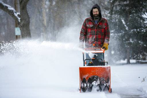 Mike Haydon snow blows the sidewalk near his home during a storm Sunday, April 15, 2018, in southwest Rochester, Minn. A deadly storm system moving through the central and southern U.S. has dumped a thick blanket of snow on parts of Minnesota, Wisconsin and South Dakota and left parts of Michigan an icy mess. (Joe Ahlquist/The Rochester Post-Bulletin via AP)