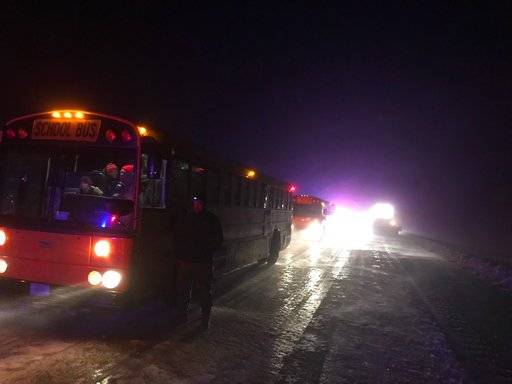 This photo provided by Nebraska State Patrol a school bus helps transport stranded motorist late Friday, April 13, 2018 near Sidney, Neb. Gov. Pete Ricketts has issued an emergency declaration to allow state funds to be used for the response to a spring blizzard that has swept most of the state.  (Nebraska State Patrol via AP)