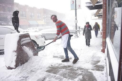 M.B. Haskett cook Mark Romanowski shovels snow in front of the restaurant, Saturday, April 14, in Sioux Falls, S.D. M.B. Haskett was one of the few restaurants open downtown Saturday.   (Briana Sanchez /The Argus Leader via AP)