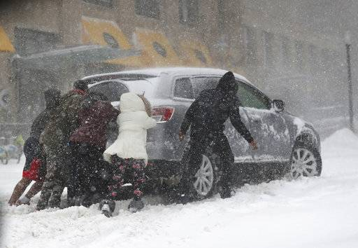 People help push a car stuck during a snowstorm, Saturday, April 14, 2018. The National Weather Service predicts 9 to 15 inches of snow across a large swath of southern Minnesota including the Twin Cities before it's all over. (David Joles/Star Tribune via AP)