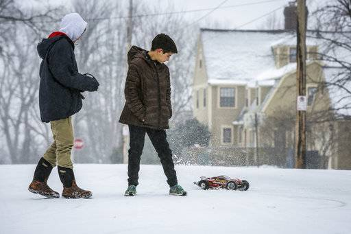 Johannes Madsen, 13, left, and friend Bode Young, 11, play with a remote control car during a storm Saturday, April 14, 2018, in Rochester, Minn.  A storm system stretching from the Gulf Coast to the Great Lakes buffeted the central U.S. with heavy winds, rain, hail and snow, (Joe Ahlquist /The Rochester Post-Bulletin via AP)