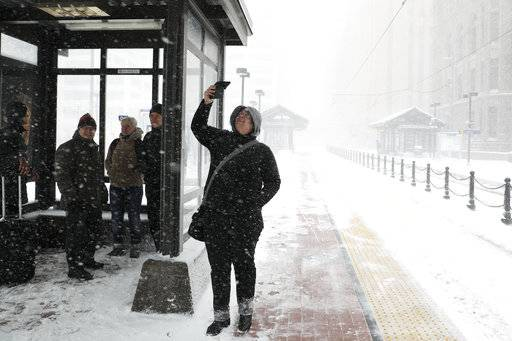Travelers at the Metro Government Center Plaza station wait for a train as the snow picked up in downtown Minneapolis, Saturday, April 14, 2018.   The National Weather Service predicts 9 to 15 inches of snow across a large swath of southern Minnesota including the Twin Cities before it's all over. (Anthony Souffle/Star Tribune via AP)