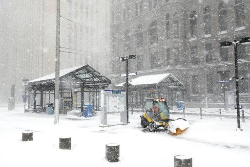 A worker tried to clear snow and ice from the Metro Government Center Plaza station as the snow picked up in downtown Minneapolis, Saturday, April 14, 2018. Authorities closed several highways in southwestern Minnesota, where no travel was advised, and driving conditions were difficult across the southern half of the state. The National Weather Service predicted that a large swath of southern Minnesota, including Minneapolis and St. Paul, would get 9 to 15 inches (23 to 38 centimeters) of snow by the time the storm blows through on Sunday, though only a few inches had fallen on the area as of midday Saturday.  (Anthony Souffle /Star Tribune via AP)