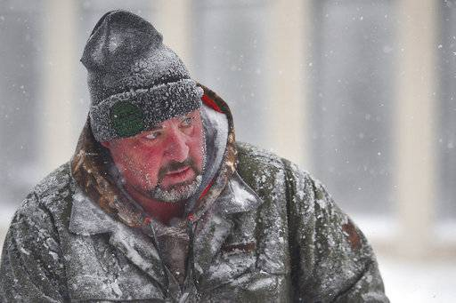 James Schoenhard, with Schoenhard Lawn Care, plows sidewalks with his team downtown Saturday, April 14, in Sioux Falls, S.D.  A storm system stretching from the Gulf of Mexico to the Great Lakes has dumped a foot of snow on parts of the upper Midwest. (Briana Sanchez/The Argus Leader via AP)