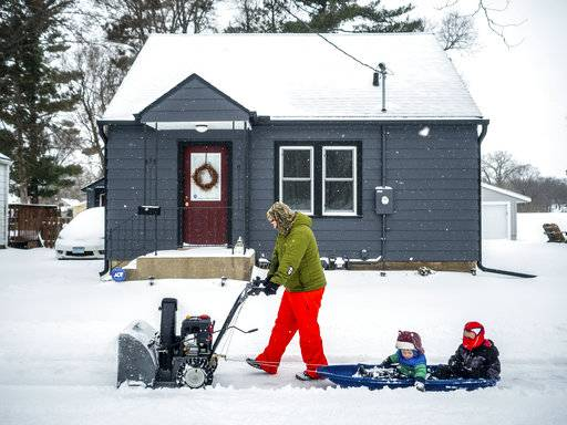 Paul Tuchtenhagen uses a snow blower to pull Leland, 2, and Ephram, 5, in a sled during a storm, Sunday, April 15, 2018, in Rochester, Minn. A deadly storm system moving through the central and southern U.S. has dumped a thick blanket of snow on parts of Minnesota, Wisconsin and South Dakota and left parts of Michigan an icy mess. (Joe Ahlquist/The Rochester Post-Bulletin via AP)