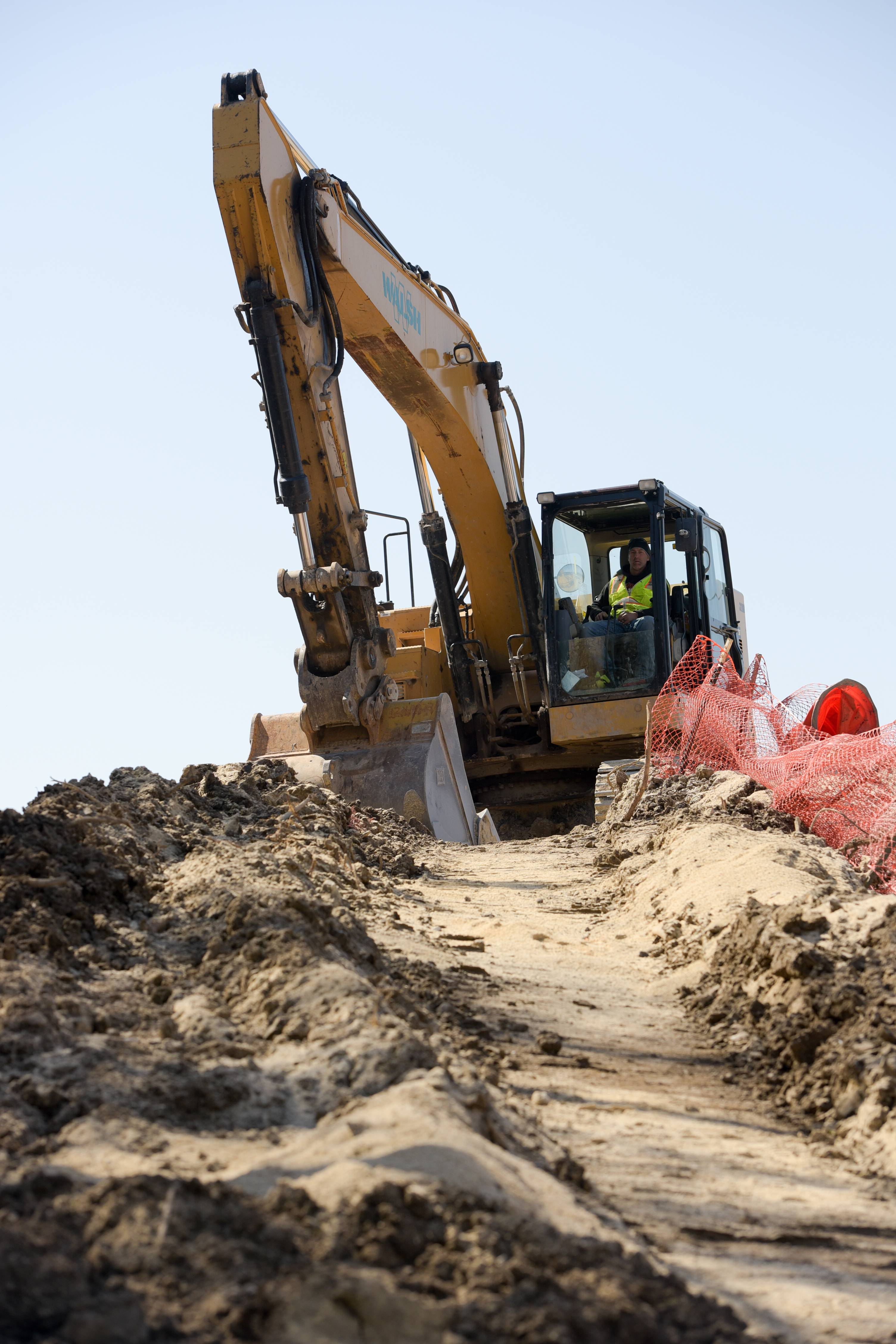 A construction worker navigates a pile of dirt as the Illinois tollway begins rebuilding and widening the east end of the Reagan Memorial Tollway (I-88) between I-290 and York Road.